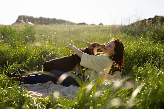 Femme pleine de coups avec un chien dans la nature