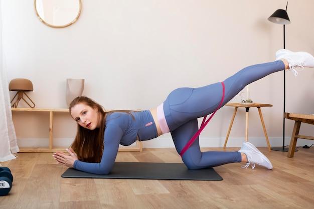 Femme pleine de coups faisant de l'exercice avec une bande élastique
