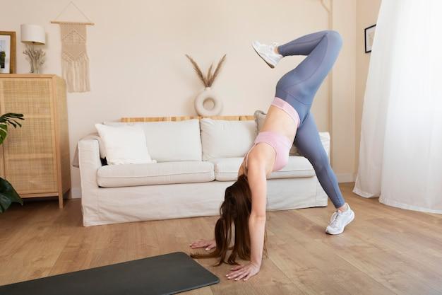 Femme pleine de coups faisant de l'exercice à la maison
