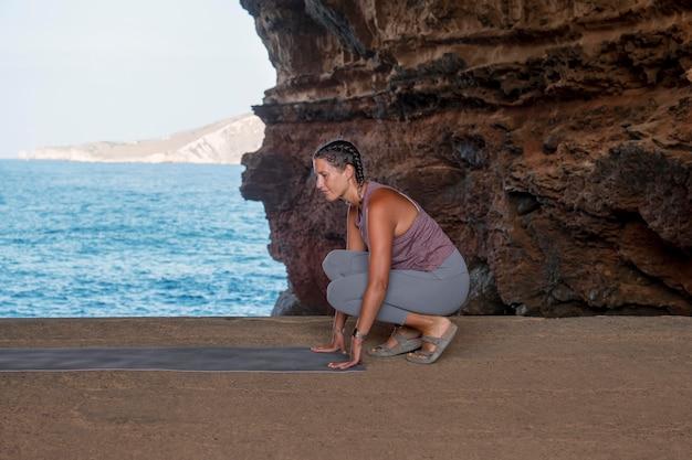 Femme pleine de coups faisant de l'exercice avec un tapis