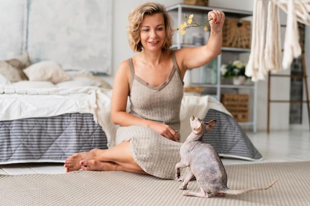 Femme pleine de coups jouant avec un chat