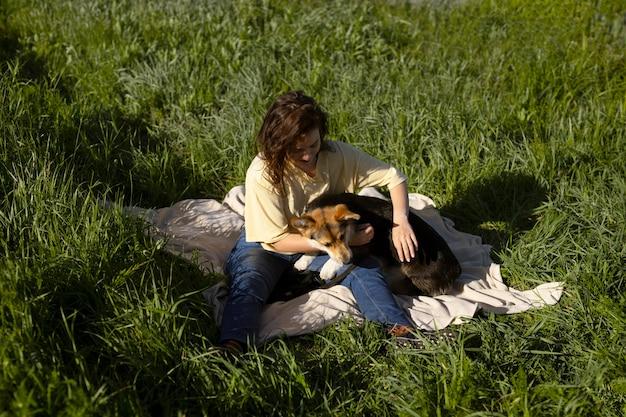 Femme pleine de coups jouant avec un chien
