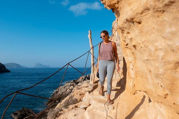 Femme pleine de coups marchant sur un rocher