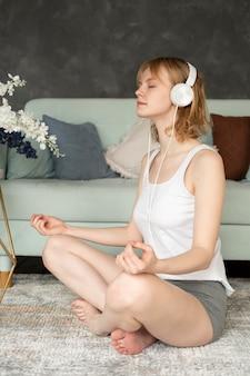 Femme pleine de coups méditant avec des écouteurs