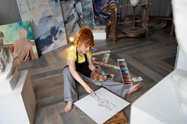 Femme pleine de coups sur la peinture au sol avec un pinceau