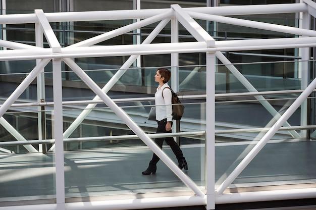 Femme pleine de coups portant un ordinateur portable et un sac à dos