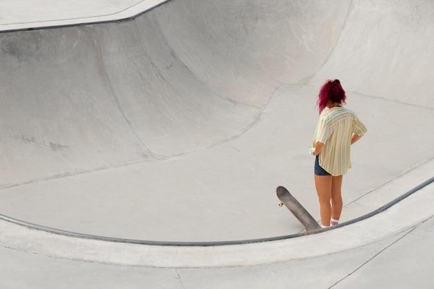 Femme pleine de coups avec skateboard