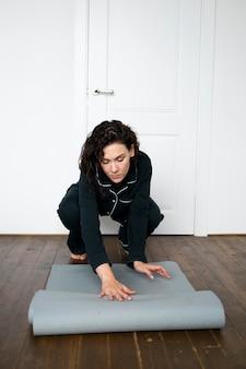 Femme pleine de coups avec tapis de yoga