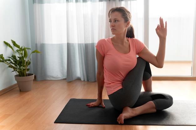 Femme pleine de coups sur un tapis de yoga