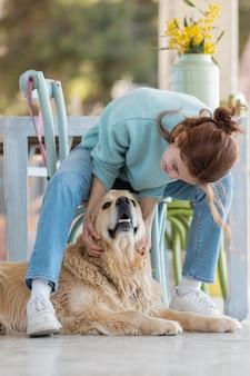 Femme pleine de tir avec chien heureux