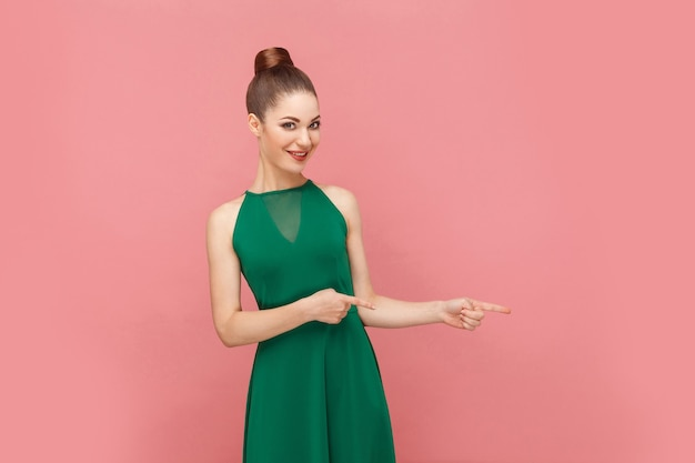 Femme à pleines dents souriant et pointant du doigt l'espace de copie. concept d'émotion et de sentiments d'expression. studio shot, isolé sur fond rose