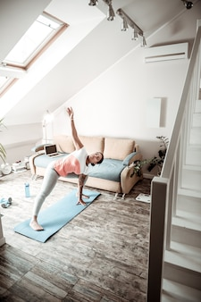 Femme pliant la taille. femme active faisant du sport dans un appartement spacieux avec de hauts plafonds et une fenêtre mansardée