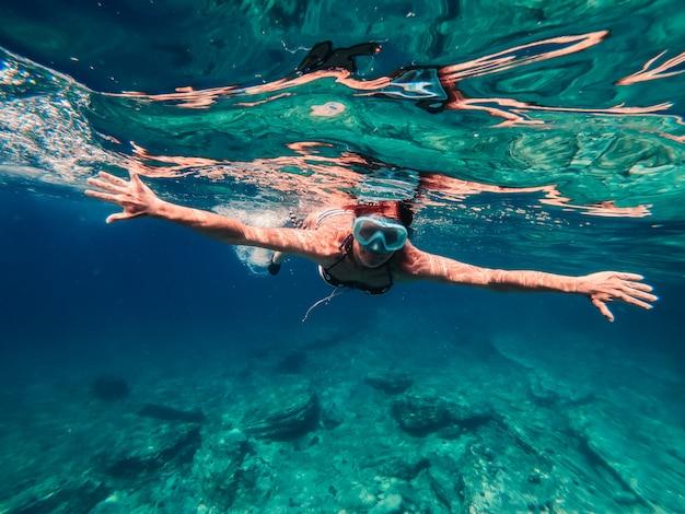 Femme plongée en apnée dans l'eau de mer peu profonde
