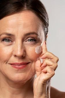 Femme plus âgée à l'aide d'une crème hydratante sur son visage