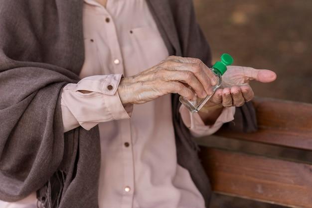 Femme plus âgée à l'aide d'un désinfectant pour les mains