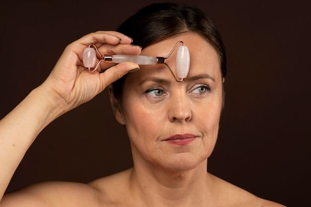 Femme plus âgée à l'aide d'un rouleau de quartz rose sur son visage