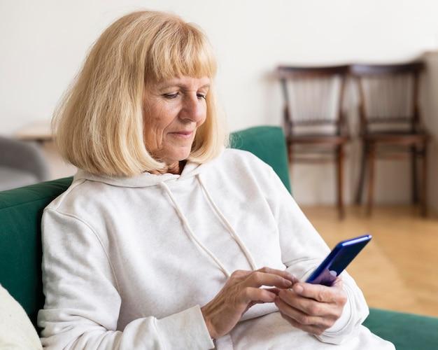 Femme plus âgée à l'aide de smartphone à la maison