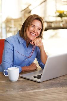 Femme plus âgée, assis à table, travaillant avec un ordinateur portable