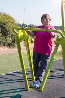 Femme plus âgée en bonne santé faisant des exercices de jambe à l'extérieur par une belle journée d'automne
