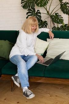 Femme plus âgée sur le canapé à la maison avec ordinateur portable