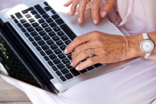 Femme plus âgée, dactylographie sur ordinateur portable