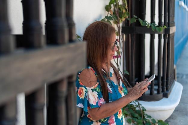 Une femme plus âgée envoie des sms ou vérifie ses e-mails, utilise une connexion internet sans fil sur son smartphone alors qu'elle est assise seule dans la rue