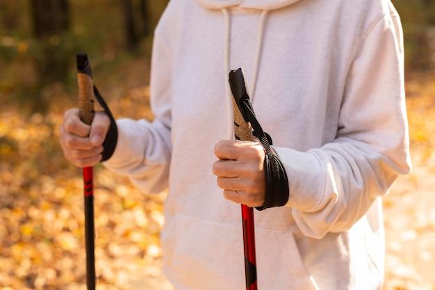 Femme plus âgée à l'extérieur avec des bâtons de randonnée