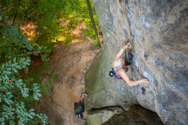 Femme plus âgée grimpeur grimpe avec des carabines et de la corde sur un mur rocheux de gros rocher.