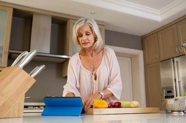 Femme plus âgée, lecture de recette dans la cuisine sur tablette
