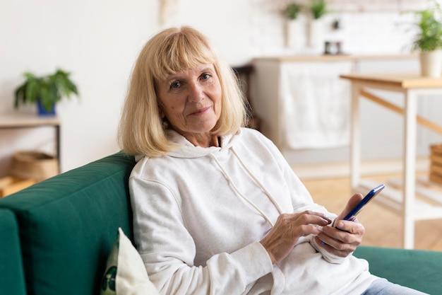 Femme plus âgée à la maison sur le canapé à l'aide d'un smartphone