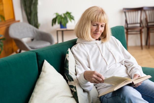 Femme plus âgée à la maison sur le canapé en lisant un livre