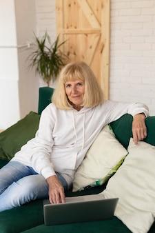 Femme plus âgée à la maison sur le canapé avec ordinateur portable