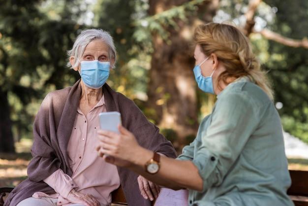 Femme plus âgée avec masque médical étant montré quelque chose sur smartphone