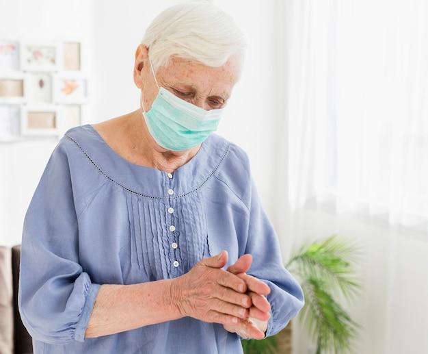 Femme plus âgée avec masque médical priant à la maison