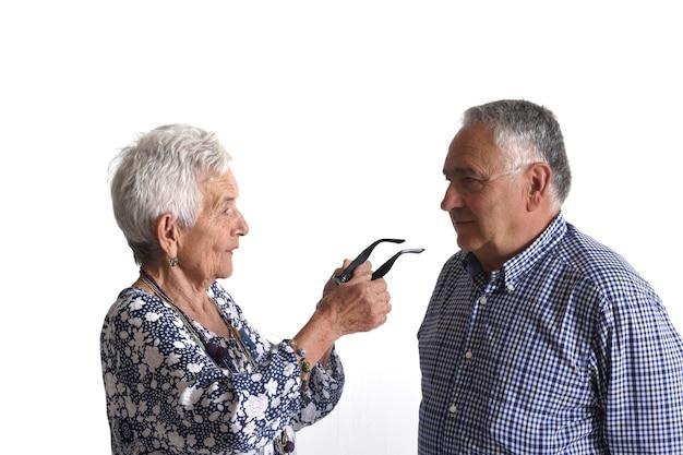 Une femme plus âgée mettant des lunettes à un homme plus âgé sur fond blanc
