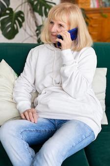 Femme plus âgée, parler au téléphone à la maison