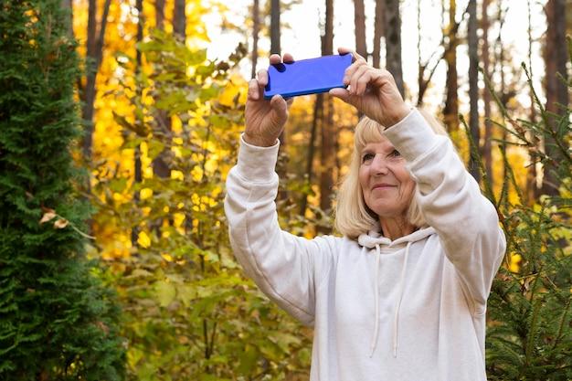Femme plus âgée à prendre des photos de la nature avec smartphone