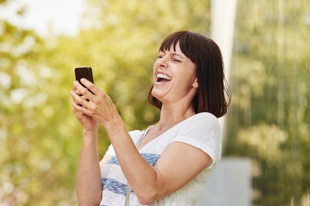 Femme plus âgée rire en regardant téléphone intelligent