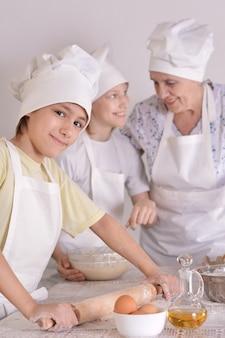 Une femme plus âgée et ses petits-enfants pétrissent la pâte ensemble