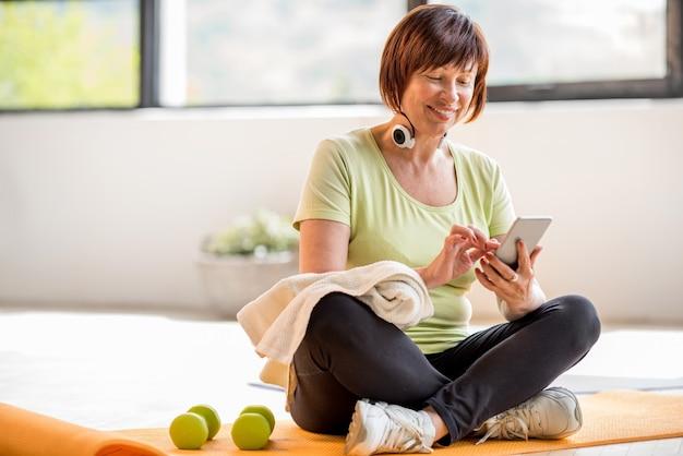 Femme plus âgée utilisant un smartphone après un entraînement sportif assis à l'intérieur à la maison ou à la salle de sport