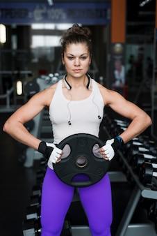 Femme avec un poids lourd en regardant la caméra