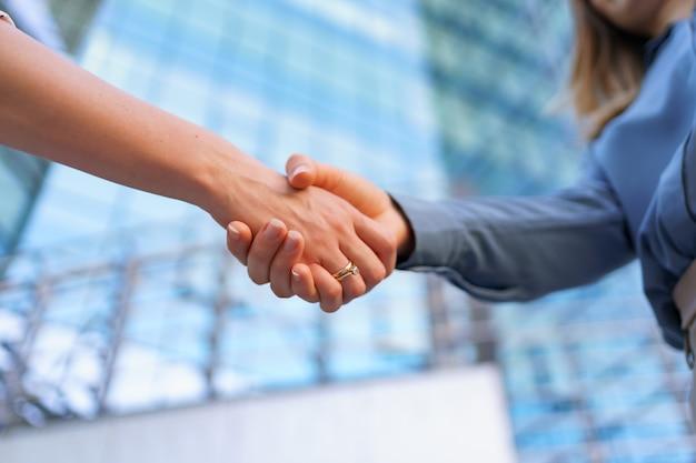 Femme de poignée de main à l'extérieur sur un bâtiment d'entreprise en verre moderne, photo en gros plan