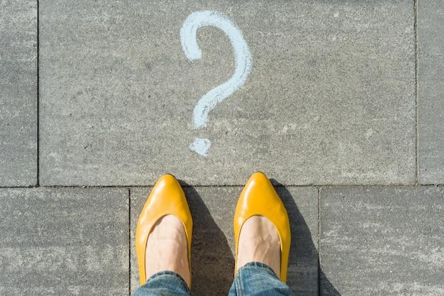 Femme avec point d'interrogation devant ses pieds