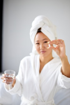 Femme sur le point de prendre un comprimé, tenant des pilules dans les mains, se concentrer sur les pilules. jolie jeune femme assise sur le lit à la maison et prenant des analgésiques avec de l'eau.