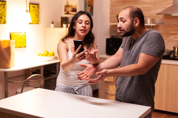 Femme pointant au téléphone tout en lisant les messages d'un mari infidèle tout en ayant un désaccord. chauffée en colère frustrée offensée irritée accusant son homme de tricherie.