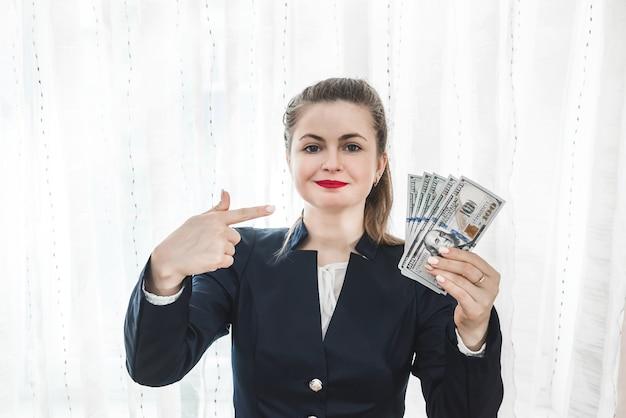 Femme pointant sur des billets en dollars dans sa main