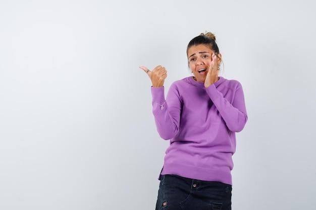 Femme pointant de côté avec le pouce en blouse de laine et à l'anxiété
