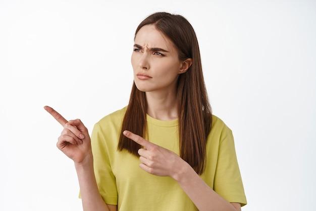 Femme pointant du doigt, regardant à gauche quelque chose d'étrange, quelle est cette expression, je ne peux pas comprendre, debout perplexe sur le blanc.