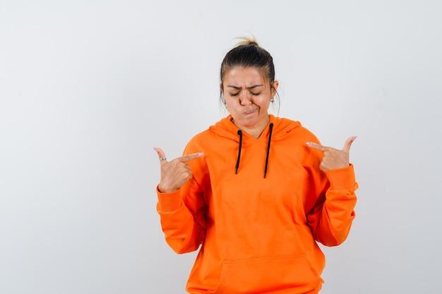 Femme pointant sur elle-même en sweat à capuche orange et à la sombre