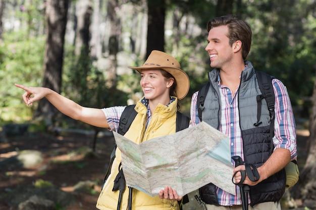 Femme pointant loin avec partenaire pendant la randonnée